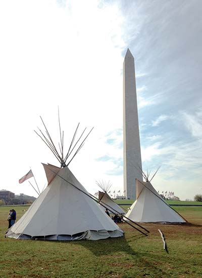 Tipi poles decorated with a flag sits along side another tipi on Sunday morning next to the Washington National Monument on the National Mall in Washington, D.C., during a Native American Church meeting to honor the nation's veterans. Veterans Day was on Tuesday. (Courtesy photo -- Jack Jackson Jr.)