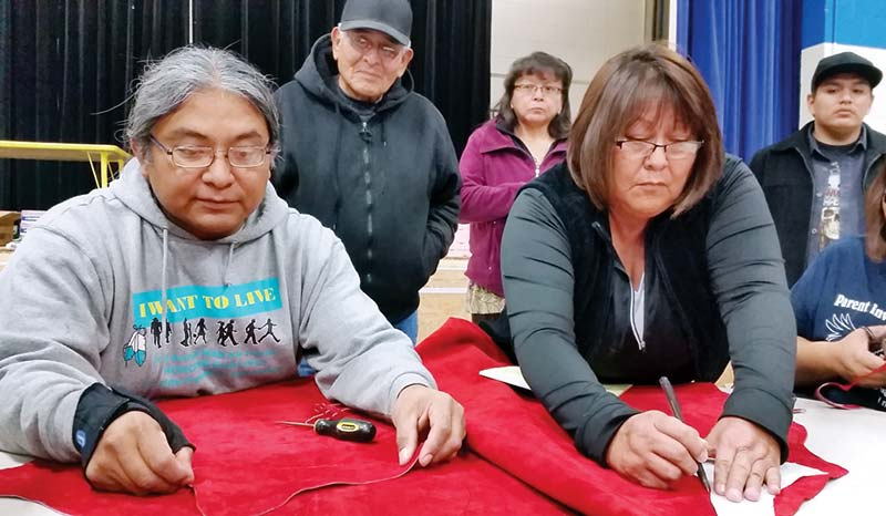 """Damien Jones from Rock Point, Ariz. talked about the importance of having a pattern cut out before cutting the red leather for your moccasin at the """"Keelchii-Moccasin Making"""" event at Hunters Point Boarding School last week as participant Pearl Tso from Chinle traces a pattern on the leather. (Times photo - Shondiin Silversmith)"""