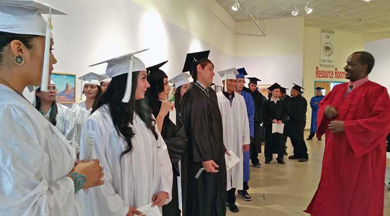 Students from the New Life Learning Center joke around with Executive Director and Pastor Benson Ndolo in the gallery of the Navajo Nation Museum waiting for their general education development commencement on Dec. 5. (Times photo — Shondiin Silversmith)