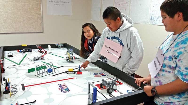 Shawndiin McCray (middle) talks a task the robot had to complete during the competition. The robot had to push the rod at a perfect 90-degree angle. (Times photo – Shondiin Silversmith)