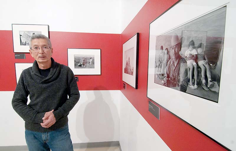 Photographer Kenji Kawano poses next to a few of his many images he has caught during his 40 years of living among the Navajo people on Friday in Window Rock. (Times photo - Donovan Quintero)