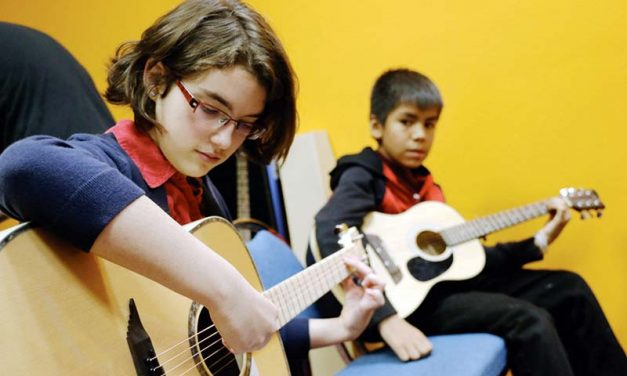 Youth learn to play, tune guitars at music workshop