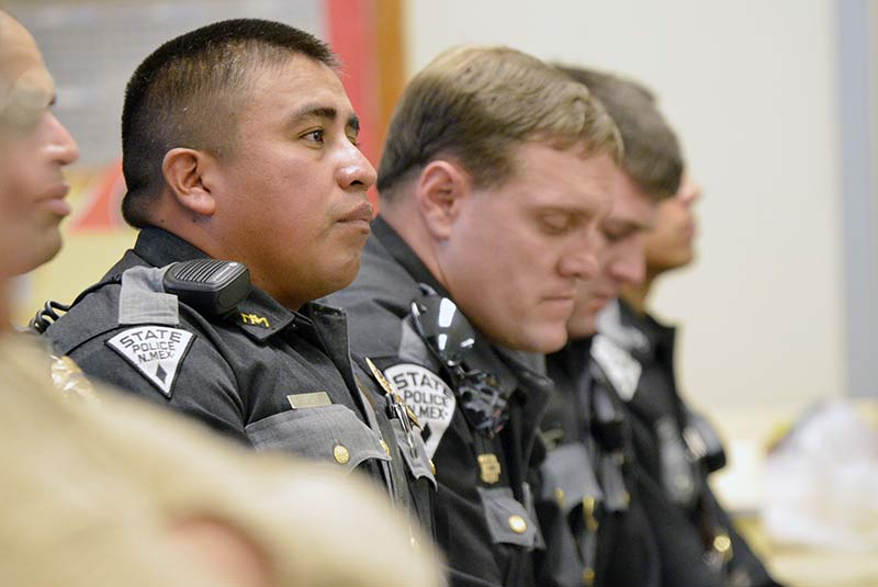 """Trooper Devon Largo with the New Mexico State Police from Pine Dale, N.M. and other troopers from the state police quietly listen on at the Crownpoint Chapter during a gathering for fallen Navajo police officer Alex Yazzie on Friday night. """"We are sorry for your loss. Thank you for being here for the family, his daughter,"""" Largo said. """"We have kids, loved ones, we come home to everyday. It is really hard to accept what happened. But be proud for what he has done for the community, his family."""" (Times photo - Donovan Quintero)"""