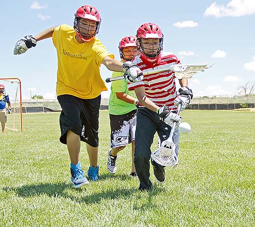 Two defenders go after the ball at the Native Vision Lacrosse clinic. Participants took part in the three-day camp held June 11-13 at Shiprock High School. (Times photo – Sunnie R. Clahchischiligi)