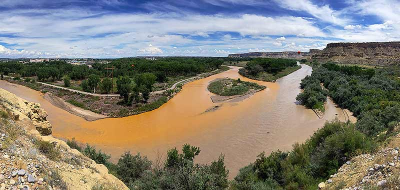 A dam breach that released a million gallons of wastewater into the Animas River on Aug. 5 colors the river orange as it merges with the San Juan River, right, on Saturday in Farmington. Navajo Nation tribal officials have been visiting community members living along the San Juan River to inform them to not use or swim in the river's water until further notice. (Times photo - Donovan Quintero)