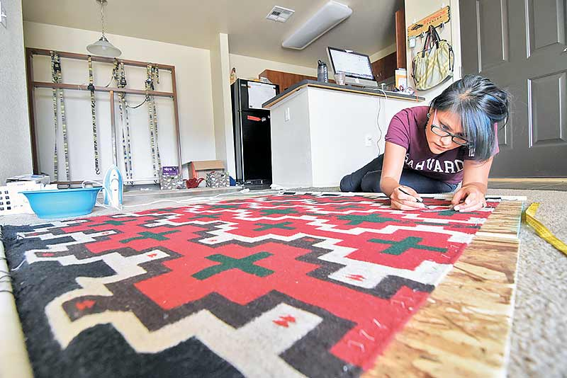 "Carrie Tsosie-Jim, originally from Sweetwater, Ariz., patiently pulls out tiny strings of wool on Tuesday at her apartment in Farmington, N.M. from her rug that took her a year to weave. Tsosie-Jim, who graduated from Harvard University with a master's in education, says the loom was a graduation gift from her late mother, Anita Tsosie, after she graduated from Stanford University with her undergraduate. ""While everyone else were getting new cars, my mom gave me a loom. I asked her why and she said 'But you could buy ten cars for the rest of your life',"" Tsosie-Jim said. ""I'm so glad my mom gave me one because it helped my brother through college, allowed us to survive."" (Times photo – Donovan Quintero)"