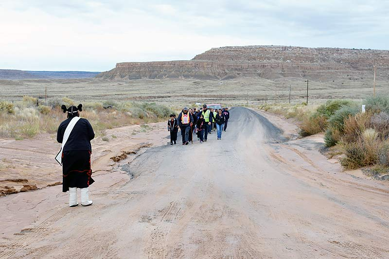 Navajo Times | Donovan Quintero John L. Tsosie, background, walks with a group of people as Miss Hopi Auri Roy, left, waits to greet them Tuesday in Kykotsmovi, Ariz.