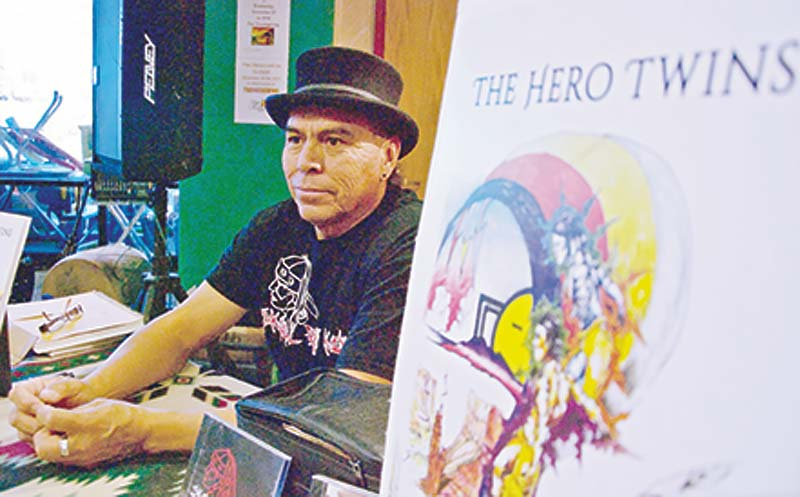 Navajo Times | Krista Allen Diné artist and musician Nolan Karras James sits behind a desk during a book signing event at Page Public Library where he made a presentation on The Hero Twins, a book he helped write and illustrate.