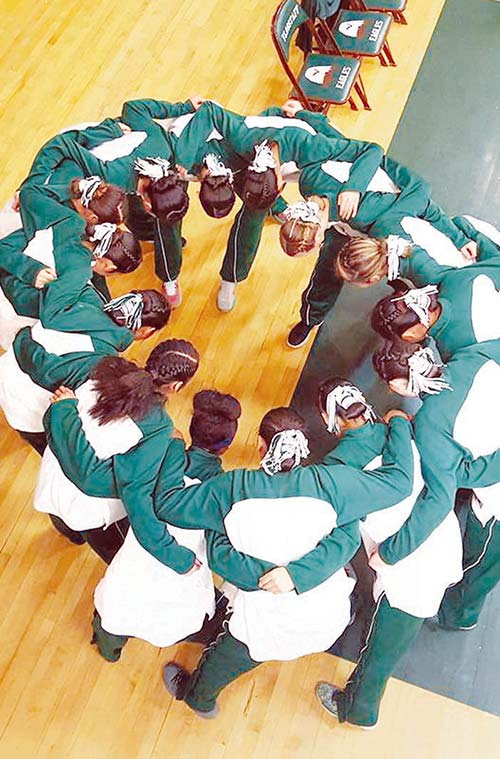 Submitted The Flagstaff Lady Eagles bow their heads in prayer before their game against Greenway Tuesday night, showing their traditional hair buns. Pauline Butler, the aunt of one of the players, said the team says a prayer in Navajo, Hebrew and English before each game.