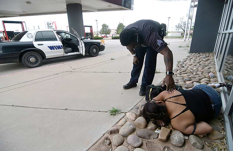 Navajo Times | Donovan Quintero Winslow police detective Sgt. Quentin Hayes attempts to wake up an intoxicated Navajo woman on Friday in Winslow.