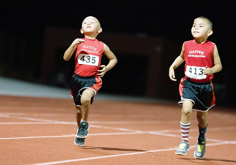 Navajo Times | Ravonelle Yazzie Cousins Joshua Morris and Maximus Fairburn run together in this year's Lori Piestewa National Native American Games track race on Saturday night in Fountain Hills, Arizona.