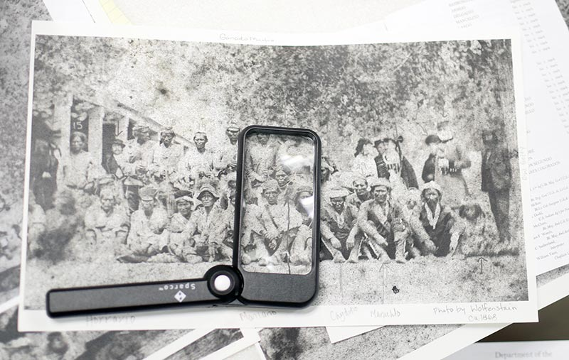 Magnifying glass over black-and-white photograph.