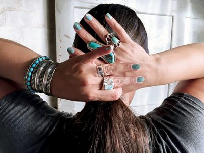 Hands with fingernails painted as turquoise, and lots of Navajo jewelry on fingers tying up hair bun.