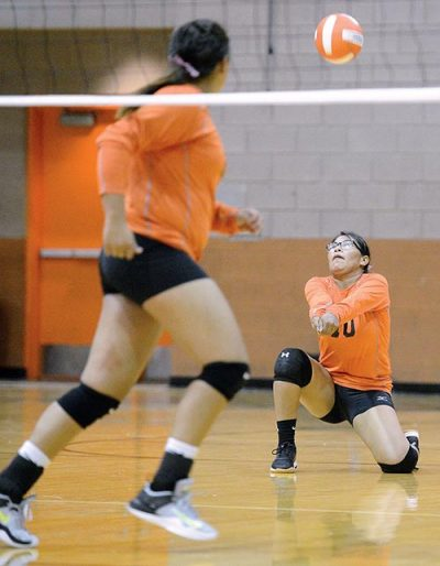Girl kneels on one knee to hit volleyball over net.