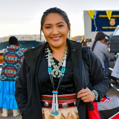 Outdoor portrait, wearing traditional Navajo clothing.