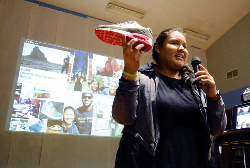 Girl holds up shoe with one hand, microphone in other hand.