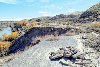 Slabs of asphalt piled onto remnants of road