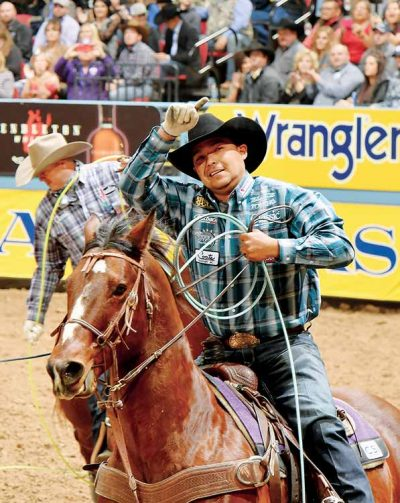 Rogers waives index finger at crownd while riding horse, holding rope.
