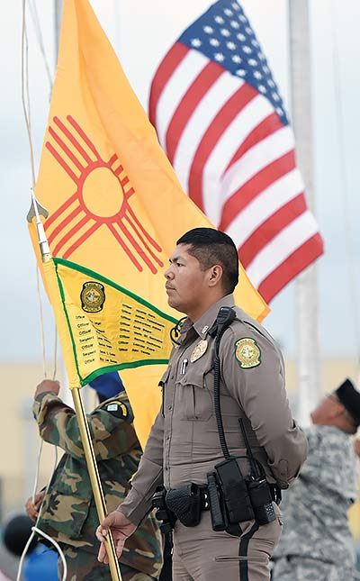 Navajo Nation officer stands next to New Mexico and U.S. flags